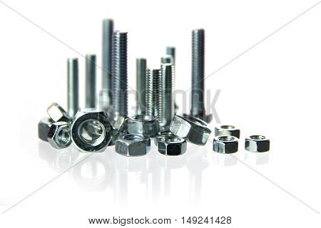 nuts and bolts standing like a skyline with long reflections on a white background concept for construction crafts and industry closeup with selected focus and a very narrow depth of field