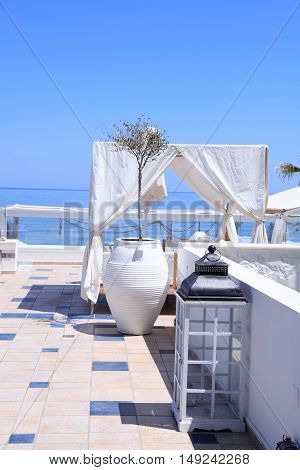 romantic terrace patio of seaside resort with outdoor furniture flower bawl and sea view, Crete, Greece. Selective focus