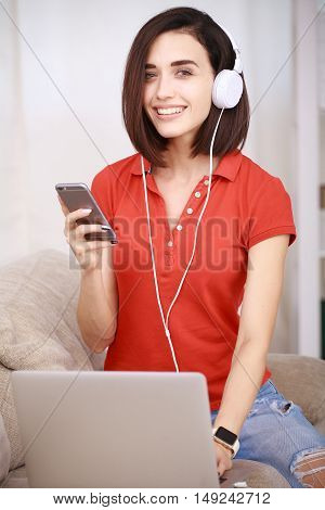 Young beautiful woman in headphones listening music and using her smartphone and laptop on couch in living room