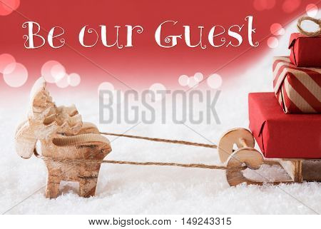 Moose Is Drawing A Sled With Red Gifts Or Presents In Snow. Christmas Card For Seasons Greetings. Red Christmassy Background With Bokeh Effect. English Text Be Our Guest