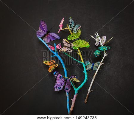 gorgeous amazing view of dried tree branches with decorated butterflies art on dark grey background