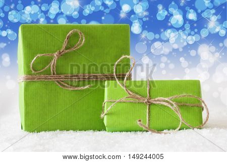 Two Green Christmas Gift Or Present On Snow. Card For Birthday Or Seasons Greetings. Natural looking Ribbon. Background With Blue Bokeh Effect