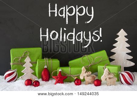 English Text Happy Holidays. Green Gifts Or Presents With Christmas Decoration Like Tree, Moose Or Red Christmas Tree Ball. Black Cement Wall As Background With Snow.