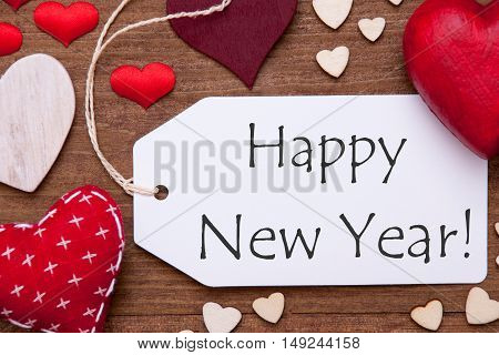 Label With English Text Happy New Year. Red Textile Hearts On Wooden Background. Flat Lay With Retro Or Vintage Style
