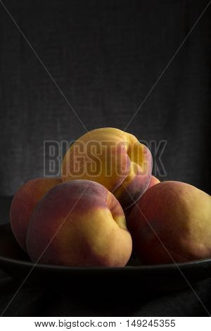 Healthy fresh peaches in a bowl and dark background