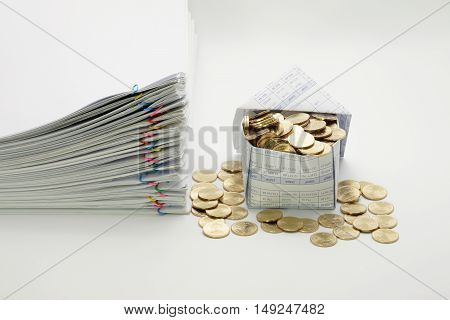 House and gold coins with pile overload document with colorful paperclip on white background.