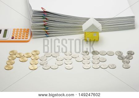 Pile overload document with colorful paperclip and house and calculator with gold and silver coins on white background.