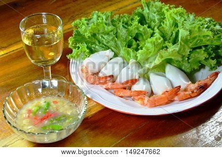 prawn stuffed squid cocktail dipping with spicy sauce and glass of champagne