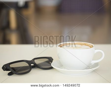 Coffee cup with glasses on wooden table soft focus