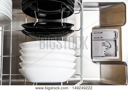 White And Black Plates In Modern Dishwasher Machine