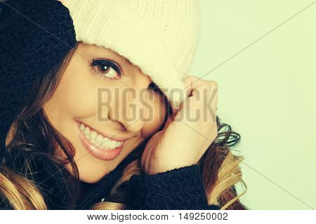Beautiful playful woman pulling beanie over her eyes