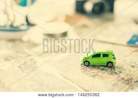 Car model and touristic map on wooden table with copy space travel concept soft focus vintage tone