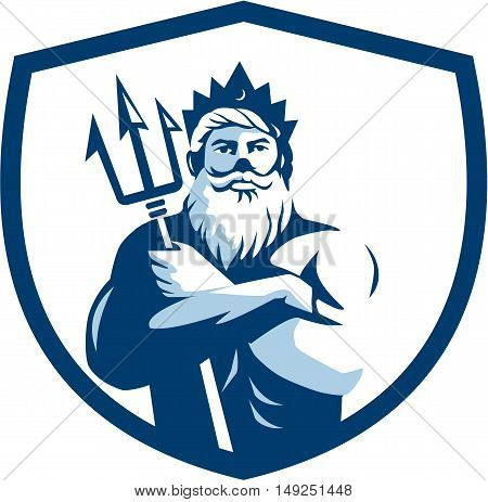 Illustration of triton mythological god arms crossed holding trident viewed from front set inside shield crest on isolated background done in retro style.