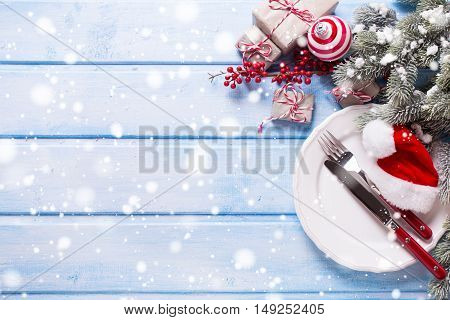 White plate knife and fork christmas decorations in white and red colors on blue wooden table. Top view. Selective focus. Place for text. Drawn snow.