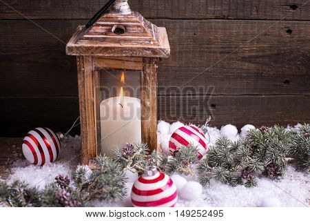 Decorative christmas composition. Burning candle in lantern christmas balls and branches fur tree on aged wooden background. Selective focus. Place for text.