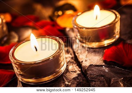 Two Romantic Tea Lights On Slate With Rose Petals And Leafs
