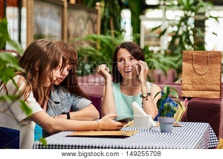 Young women or colleagues sitting in a cafe or restaurant, and choosing the menu and calling with phone