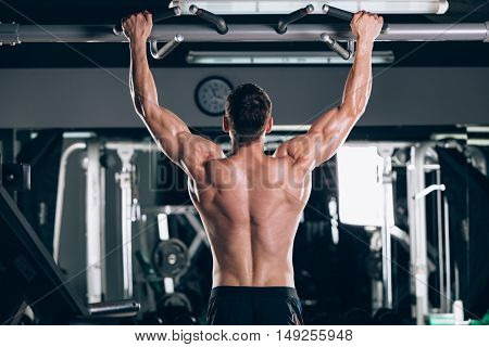 Athlete muscular fitness male model pulling up on horizontal bar in a gym.