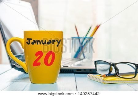January 20th. Day 20 of month, Calendar on cup morning coffee or tea, freelancer workspace background. Winter time. Empty space for text.