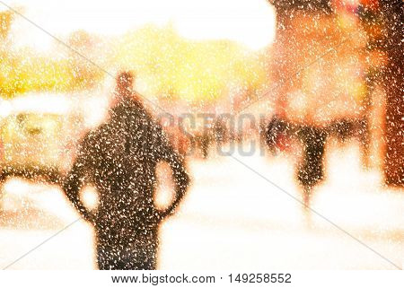 Winter city commuters with snow. Blurred image of workers going back home after work. Unrecognizable faces, bleached effect.