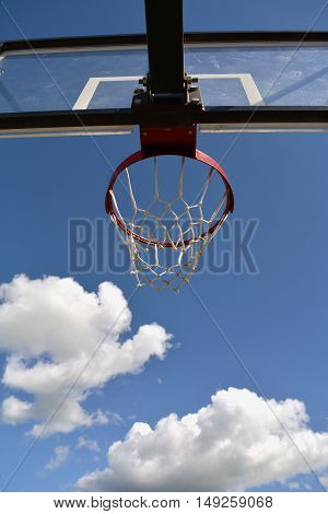 Basketball stand with a hoop outdoors against blue sky