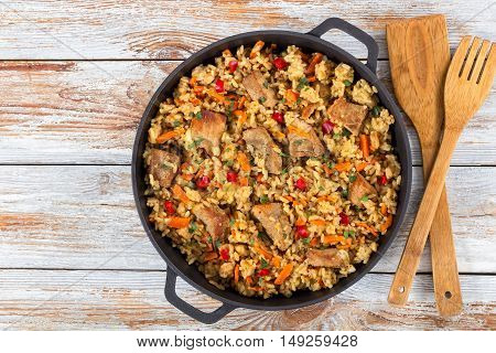 Homemade prepared paella with meat pepper vegetables and spices in iron stewpan on old planks wooden spatula and fork on background close-up view from above