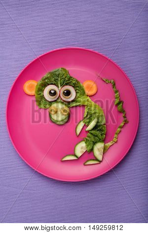 Monkey made of vegetables on plate and fabric