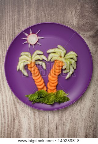 Palm tree made of fresh vegetables on plate and desk
