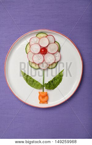 Flower made of fresh vegetables on plate and fabric