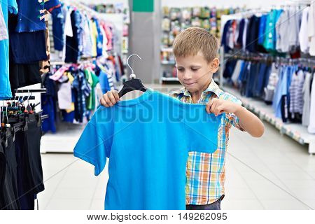 Little boy chooses a shirt in a clothing store