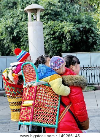 Fenghuang ,December-28  2014, Lovely baby enjoy in basket carried by mothers at Phoenix Hall park in morning,Hunan,China