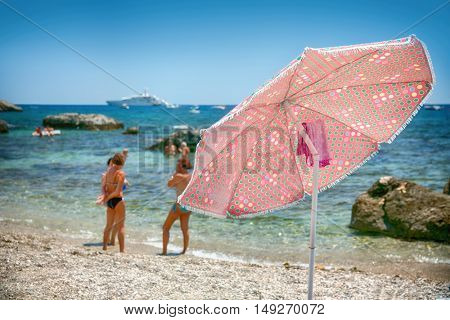 The Umbrella on a pebble beach in the background with people, and the cruise ships