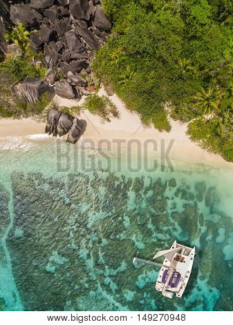 Aerial photo of Seychelles tropical beach Anse Source D Argent at La Digue island with catamaran boat