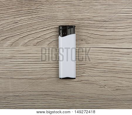 Black-and-white blank gas lighter on a wooden background
