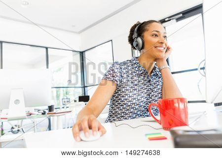 Portrait of smiling afro-american office worker sitting in offfice with headphones