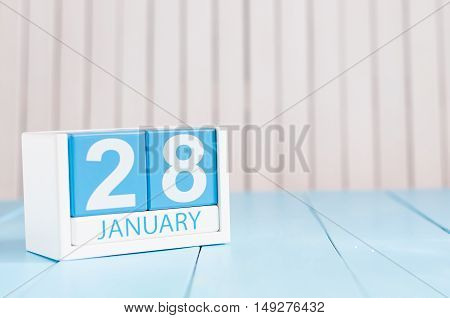 January 28th. Day 28 of month, calendar on wooden background. Winter at work concept. Empty space for text.