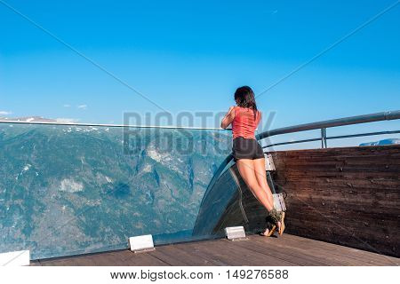 Woman enjoying scenics from Stegastein Viewpoint in a summer sunny day, Flam, Norway