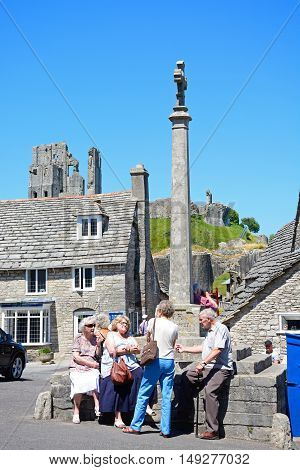 CORFE, UNITED KINGDOM - JULY 19, 2016 - Tourists around the stone cross in the village centre with the castle to the rear Corfe Dorset England UK Western Europe, July 19, 2016.
