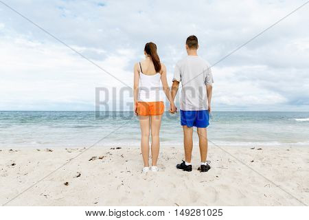 Young couple looking thoughtful while standing next to each other on beach