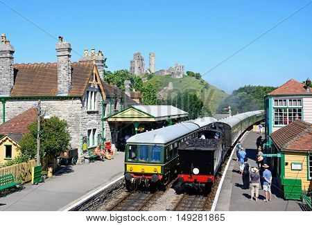 CORFE, UNITED KINGDOM - JULY 19, 2016 - LSWR T9 Class 4-4-0 steam train and BR Class 108 diesel train in the railway station with the castle to the rear Corfe Dorset England UK Western Europe, July 19, 2016.