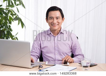 Smiling businessman at his desk with laptop and documents in his office