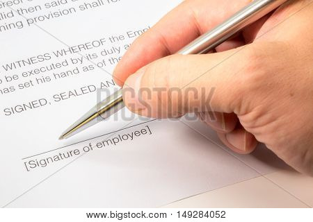 Close up of an employment contract with a line and a hand signing it with a silver pen