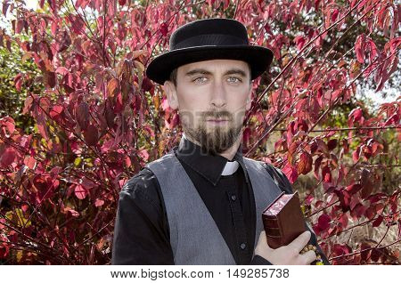 Young bearded priest on red tree background
