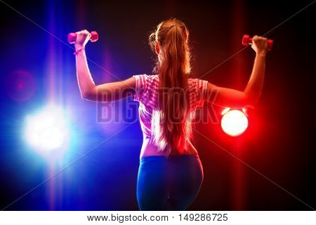 Sports fitness girl with slim figure works dumbbells in multi-colored rays of the fitness room. Back view. Sport girl with long hair.