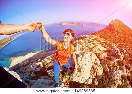 couple of travelers with backpack standing on the cliff against sea and blue sky at early morning. Balos beach on background, Crete, Greece. a man helping a woman climb on the rock extends her hand