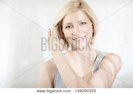 Closeup portrait of happy young blonde woman smiling with hand in hair.