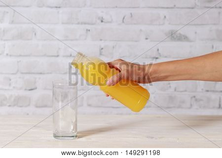 Glass with ice and girls's hand with bottle of juice