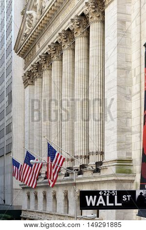 Wall street sign in New York with New York Stock Exchange background on Circa June, 2016 in New York, USA