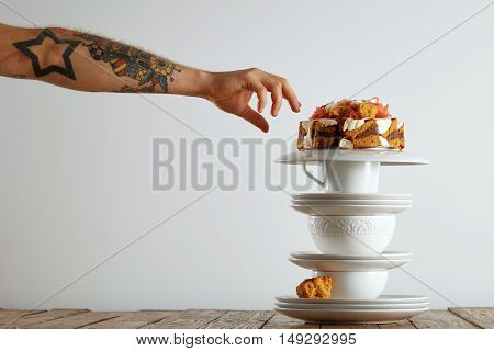tattooed man's hand reaching out to grab a piece of cake balanced on a pyramid of white teaware