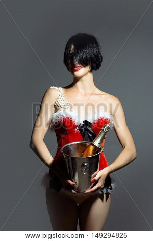 young sexy new year woman or girl with and red lips on pretty face in christmas santa claus holiday costume holds metallic pail with wine or champagne bottle in studio on grey background